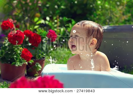 Cute Funny Small Baby Boy Bathing Outdoor On Green Lawn Among Flowers