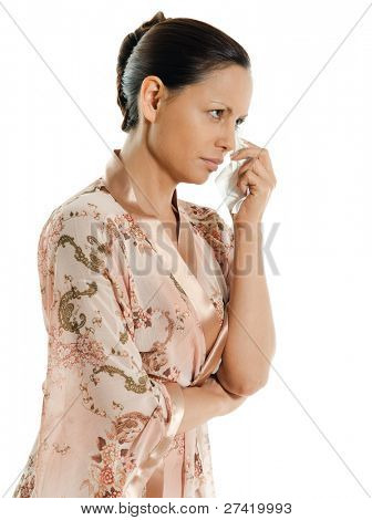 Portrait of pensive Asian woman crying and looking away in studio isolated on white background