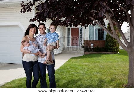 Portrait of happy Couple stehen mit ihren Kindern in front of house