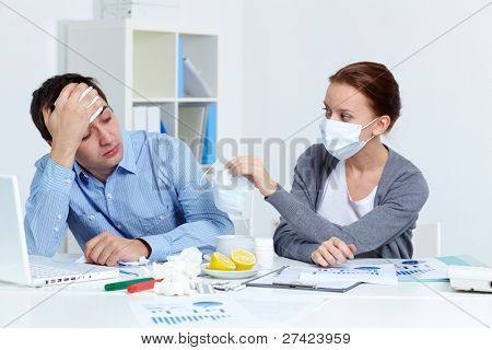 Image of sick businessman looking at his partner in mask offering him to put on one in office