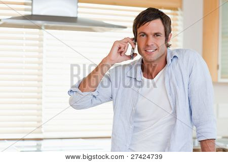 Happy man making a phone call in his kitchen