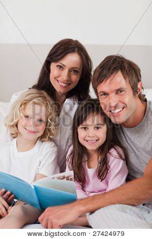 Portrait of a happy family reading a book in a bedroom