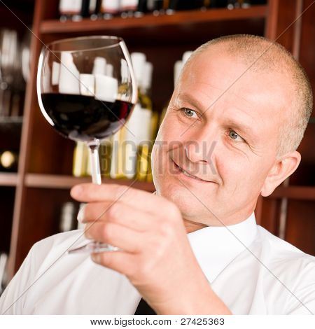 At the bar - senior barman hold glass red wine degustation