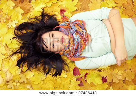 Beautiful Woman Lying In Leaves Wearing Colourful Scarf