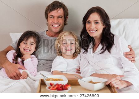 Happy family having breakfast together in a bedroom