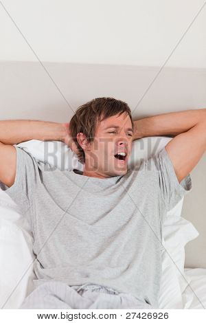 Portrait of a man yawning in his bedroom