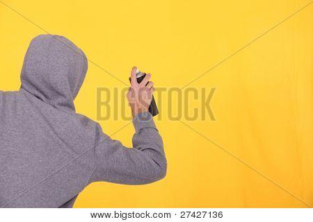 Man in a hoodie spray painting