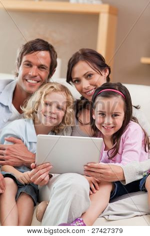 Portrait of a family using a tablet computer in a living room