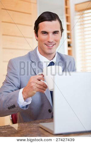Smiling young businessman with laptop and coffee