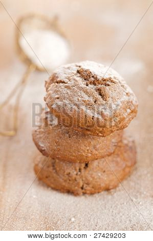 soft ginger cookies three stacked and dusted on wooden table, sieve with caster sugar on background, shallow dof