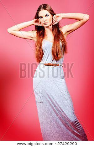 Retrato de una mujer joven atractiva sobre fondo rosa.