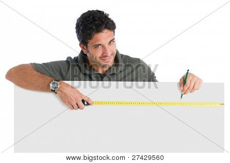 Happy satisfied young man measuring with tape a blank sign ready for your text, isolated on white background