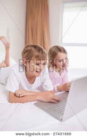 Retrato de crianças usando um notebook em um quarto