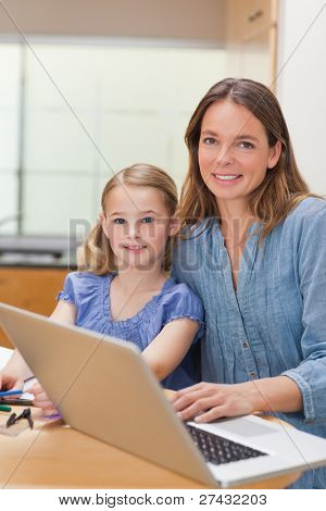 Portrait of a girl doing her homework while her mother is working with laptop in a kitchen