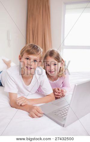 Retrato de crianças usando um laptop em um quarto