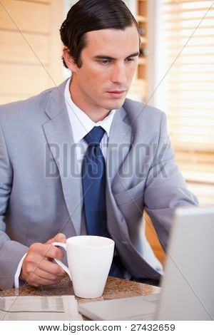 Young businessman with coffee on his laptop