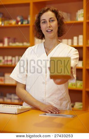 Female pharmacist behind counter explaining usage of medicine