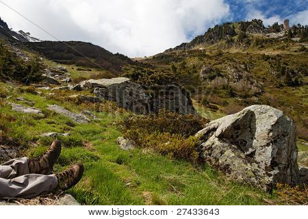 Hiker relaxing with his feet stretched in the French Alps