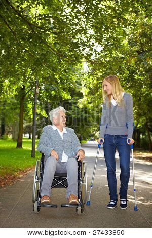 Two women in wheelchair and on crutches talking in a park
