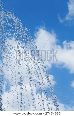 Drops of a clear water against the blue sky with clouds