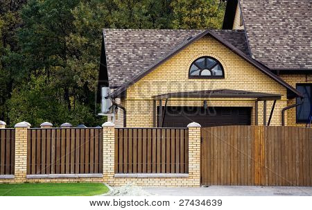 brick house and fence in an environment of vegetation and trees