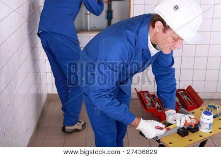 Encanadores trabalhando em uma sala de azulejos