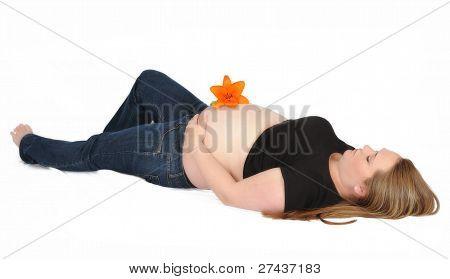 strahlende schwangere Frau Handauflegen mit Blumen auf Magen zurück.