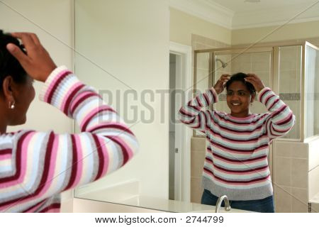 Woman Doing Hair In Mirror