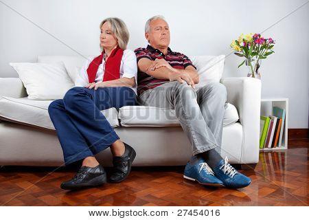 Full length of senior couple sitting on sofa after quarrel