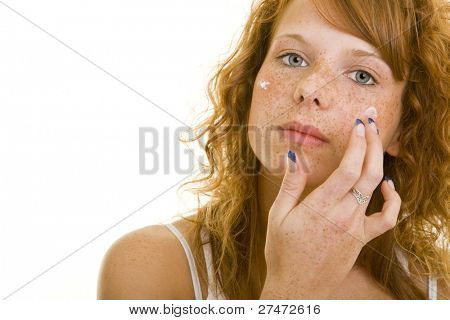 Young redheaded woman using lotion