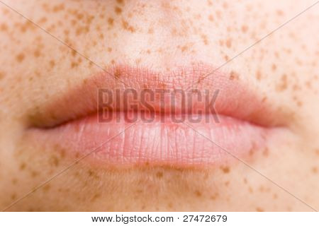 Mouth of a woman with freckles