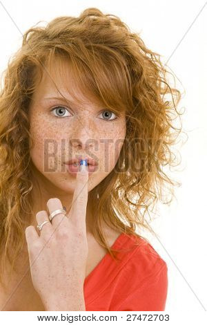 Young redheaded woman holding her index finger in front of her mouth