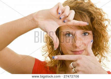 Young redheaded woman looking through her fingers