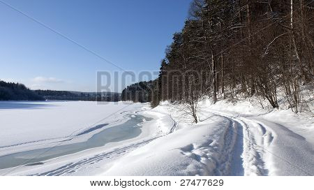 Snow on a river in winter. Track of humans in the riverside.