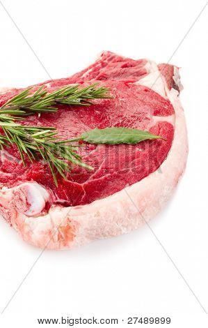 raw T-bone with herbs close up