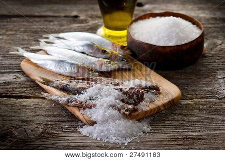 sardines with salt on wood background