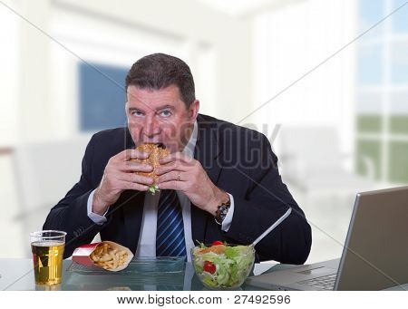 man at office working and eat unhealthy fast food