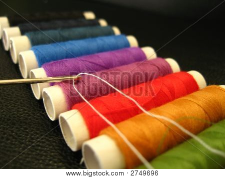Needle With Thread On Coloured Background