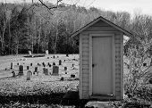 pic of funeral home  - Wooden shed in graveyard under trees in a field - JPG