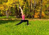 foto of virabhadrasana  - Woman exercises in the autumn forest yoga virabhadrasana pose - JPG