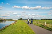 Two Unidentified People Cycle On A Cycle Path At The Top Of A Dike Along A Narrow River At The Dutch poster