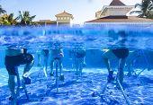 Touristen Doing Aqua Aerobics On Exercise Bikes In Swimming Pool Tropical Hotel poster