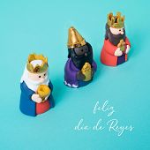 the three wise men and the text feliz dia de reyes, happy epiphany day written in spanish, on a blue poster