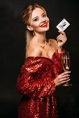 Smiling Attractive Girl In Red Shiny Dress Holding Joker Card And Glass Of Champagne Isolated On Bla poster