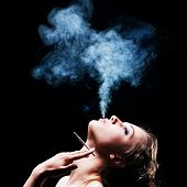 image of tobacco smoke  - woman smokes in the dark - JPG