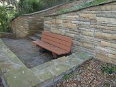 pic of fieldstone-wall  - Photo of a masonry retaining wall with a staircase and a park bench - JPG