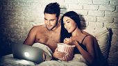 Couple Using Laptop Lying On Bed Watching Movie. Spending Time With Each Other. Woman And Man Lying  poster