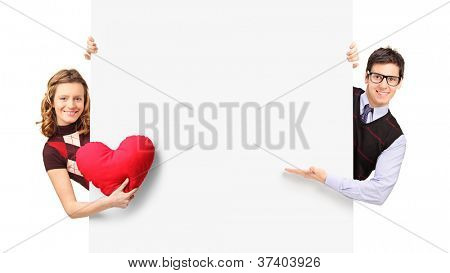 Young couple peeking out of a banner isolated on white background