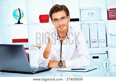 Handsome businessman at the office holds out his hand for a handshake.