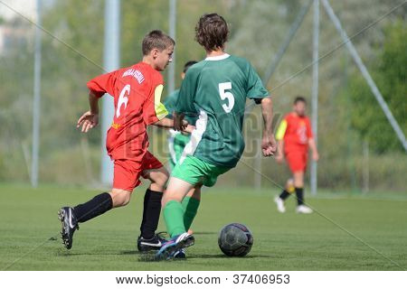 KAPOSVAR, HUNGARY - SEPTEMBER 22: Richard Kovacs (red 6) in action at the Hungarian Championship under 15 game between Rakoczi (green) and Mezga FC (red) September 22, 2012 in Kaposvar, Hungary.